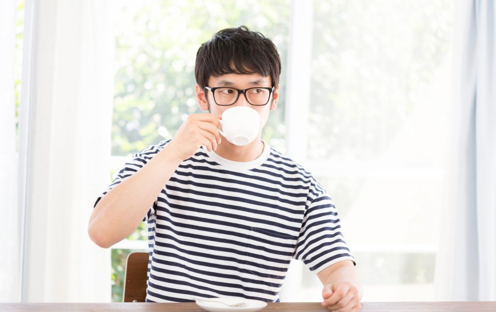 コーヒーを飲むボーダーの男性